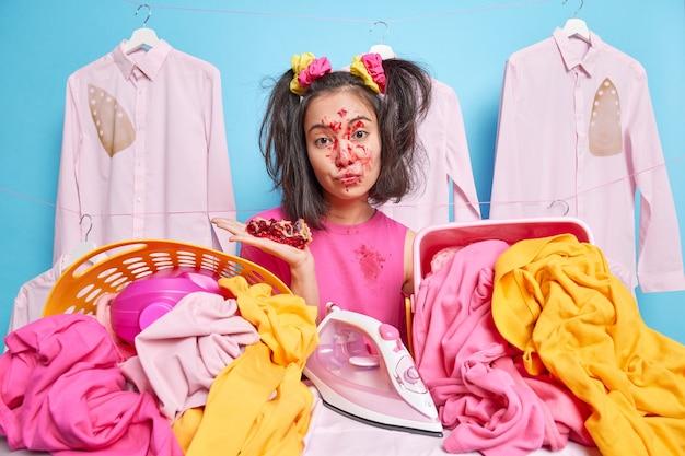 Serieus aziatisch meisje heeft twee poses in paardenstaarten bij twee manden met wasgoed