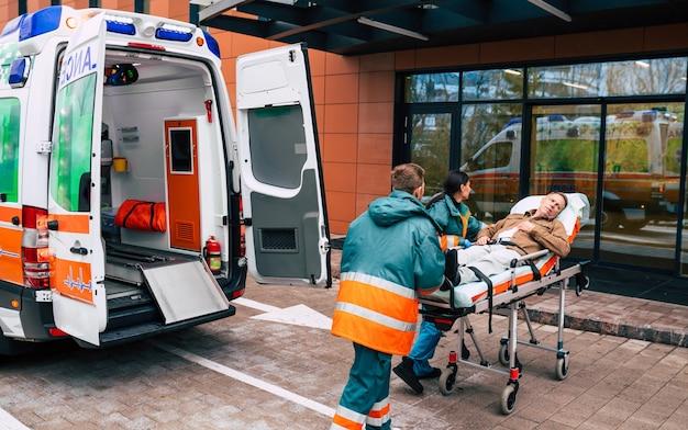 Serieus en professioneel team van artsen in de ambulance die tijdens een noodsituatie een patiënt naar het ziekenhuis brengen.