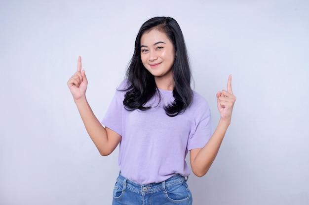 Serieus gelukkige aziatische vrouw met haar vinger naar boven gericht en geïsoleerd op een lichte witte bannerachtergrond met kopieerruimte