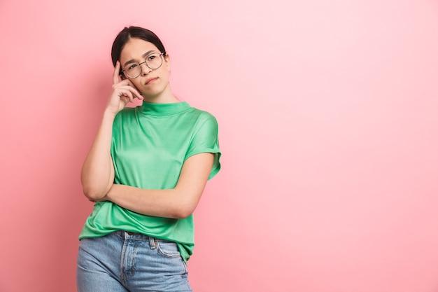 Serieus jong meisje met een ronde bril die denkt en opzij kijkt geïsoleerd over roze muur