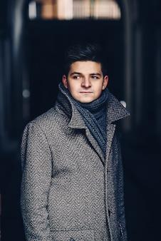 Serieus jonge man in warme jas op een donkere straat