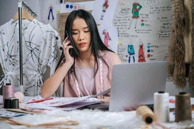 Serieus jonge ontwerper die met smartphone praat terwijl hij een laptop gebruikt om samen te controleren