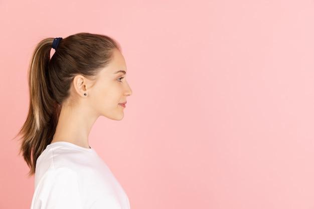 Serieus, kalm en beheerst. portret van de blanke jonge vrouw geïsoleerd op roze studio muur met copyspace.