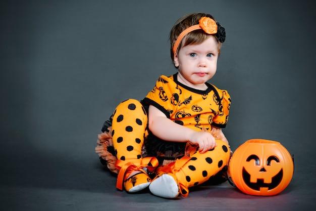 Serieus, klein meisje in halloween-kostuum met pompoensnoepkom. grappig kind in de studio, grimas en horror tijdens de vakantie.