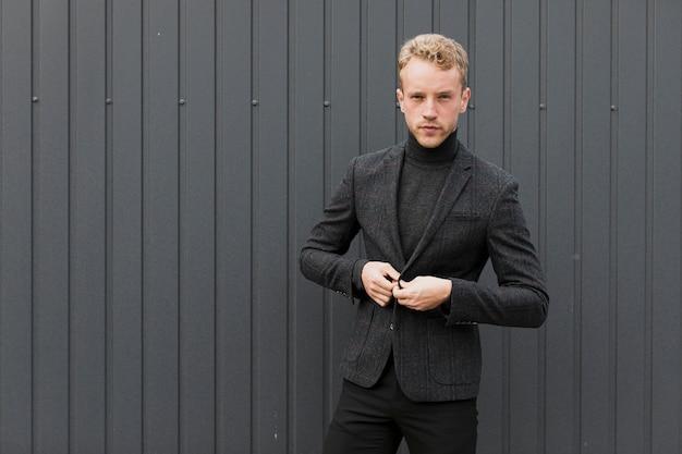 Serieus man in het zwart in de buurt van een grijze muur