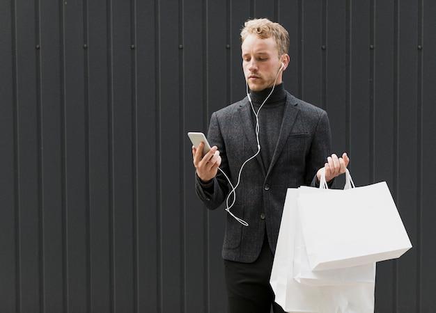 Serieus man in het zwart met koptelefoon en smartphone