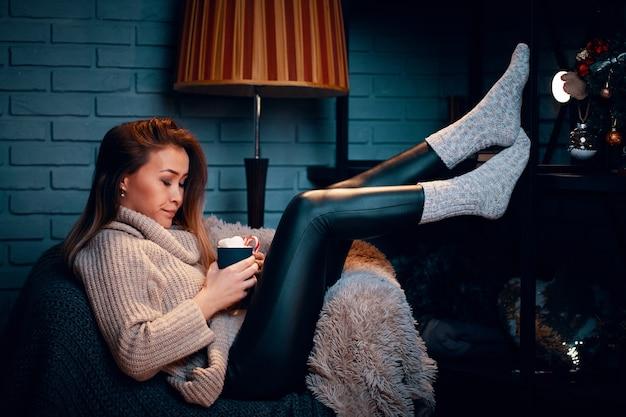Serieus meisje in trui op stoel mok warme chocolademelk met marshmallows gestreepte staande lamp grijze bric...
