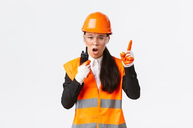 Serieus ogende aziatische vrouwelijke industrieel ingenieur, technicus in veiligheidshelm en uniform commandoconstructieteam met walkie-talkie, iemand uitleggen of uitschelden met radiotelefoon