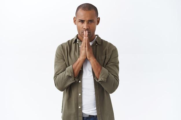 Serieus ogende, hoopvolle jonge afro-amerikaanse man die bidt voor zijn familie, komt goed tijdens covid19 pandemie