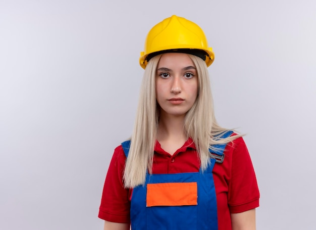 Serieus ogende jonge blonde ingenieur bouwer meisje in uniform kijken op geïsoleerde witte ruimte met kopie ruimte