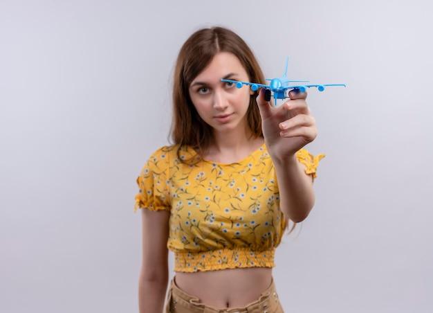 Serieus op zoek naar jong meisje modelvliegtuig uitrekken op geïsoleerde witte ruimte met kopie ruimte