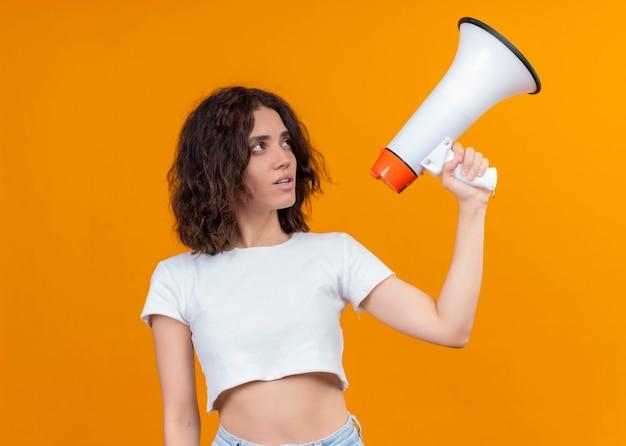 Serieus op zoek naar jonge mooie vrouw met spreker en ernaar kijken op geïsoleerde oranje muur met kopie ruimte