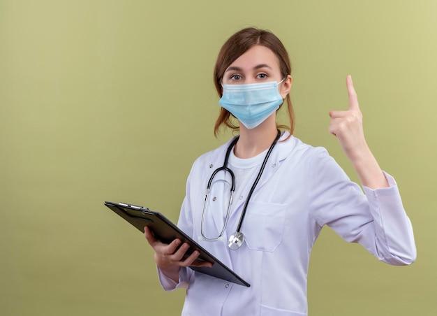 Serieus op zoek naar jonge vrouwelijke arts die medische mantel, masker en stethoscoop draagt ?? die klembord benadrukt op geïsoleerde groene ruimte