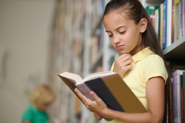 Serieus schoolmeisje gericht op het lezen van een boek