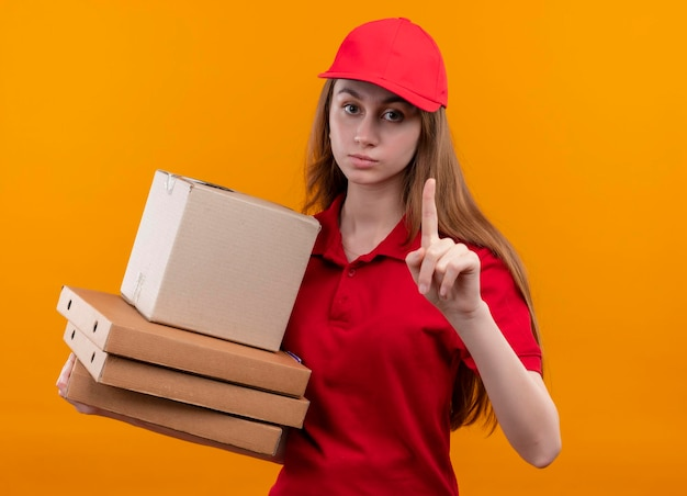 Serieus uitziend jong bezorgmeisje in rode uniforme holdingsdoos en pakketten met opgeheven vinger op geïsoleerde oranje ruimte