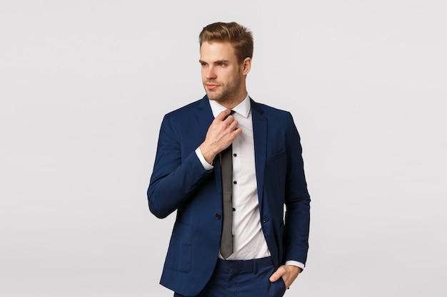 Serieus uitziende brutale zakenman in blauwe classis-pak, stropdas aanpassen en wegkijken, hand in zak houden, zich klaarmaken voor werk, wachten op taxi in binnenstad om zakelijke bijeenkomst te gaan, partners begroeten