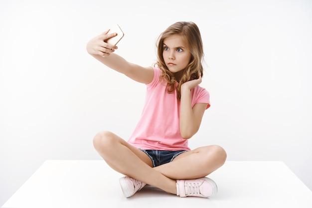 Serieus uitziende grappige schattige blonde europese tienermeisje zittend op de vloer met gekruiste benen, strek arm smartphone uit om grimas te proberen, boos zelfverzekerde uitdrukking te maken, selfie te nemen, te fotograferen