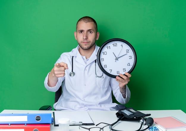 Serieus uitziende jonge mannelijke arts die medische mantel en stethoscoop draagt ?? die aan bureau zit met uitrustingsstukken die klok vasthouden en naar voorzijde wijst geïsoleerd op groene muur