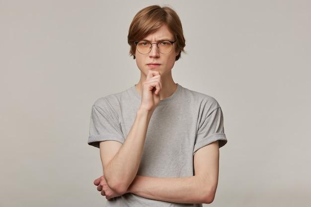 Serieus uitziende man, denkende man met blond haar. grijze t-shirt en bril dragen. mensen en emotie concept. fronst en raakt zijn kin aan.