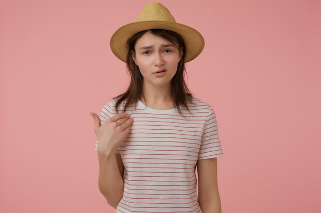 Serieus uitziende vrouw, zelfverzekerd meisje met lang donkerbruin haar. het dragen van t-shirt met rode strepen en hoed. naar zichzelf wijzend. geïsoleerd over pastelroze muur