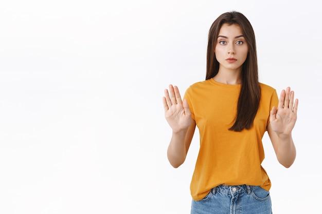 Serieus uitziende zelfverzekerde knappe vrouw in geel t-shirt, handen opstekend in stop-, taboe- of verbodsbeweging, kijk terughoudend en zelfverzekerd, verbieden of beperken, iets afwijzen