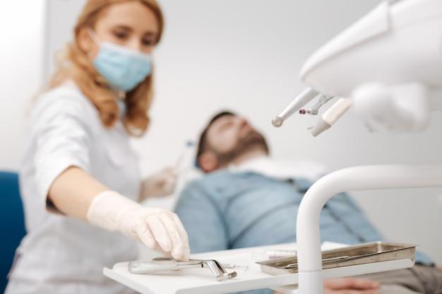 Serieus voorbereide, vooraanstaande tandarts die naar haar steriele gereedschap reikt terwijl ze het nodig heeft voor het trekken van de tand van de patiënt