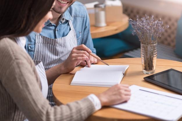 Serieus werk. gelukkig jonge man en vrouw glimlachend en zittend aan tafel tijdens het werken met papieren.