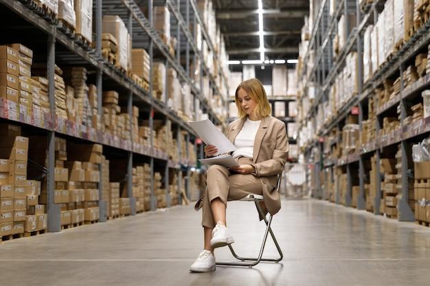 Serieus zakenvrouw of supervisor in een beige pak documenten controleren, zittend op een stoel bij lege faciliteit opslag / magazijn