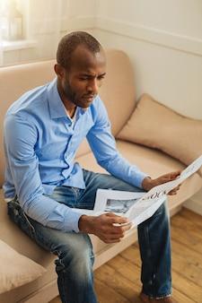 Serieus zijn. geconcentreerde ernstige afro-amerikaanse man die een krant vasthoudt en leest terwijl hij op de bank zit
