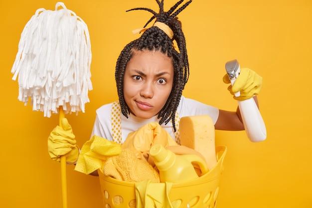 Serieuze afro-amerikaanse huisvrouw met vlechten kijkt aandachtig