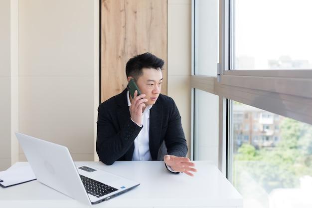 Serieuze aziatische zakenman gebruikt mobiele telefoon om te communiceren