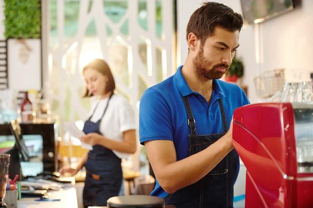 Serieuze barista die koffie maakt wanneer serveerster bonnen op de achtergrond beheert