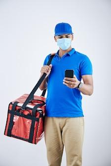 Serieuze bezorger met beschermend masker die het adres van de klant controleert in een mobiele applicatie waar hij eten moet bezorgen