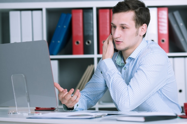 Serieuze bznesmen praten aan de telefoon op kantoor