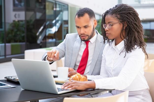 Serieuze collega's kijken en bespreken presentatie