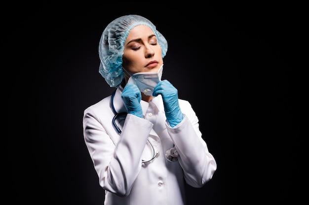 Serieuze dokter dame na nachtdienst geïsoleerd op zwarte kleur achtergrond