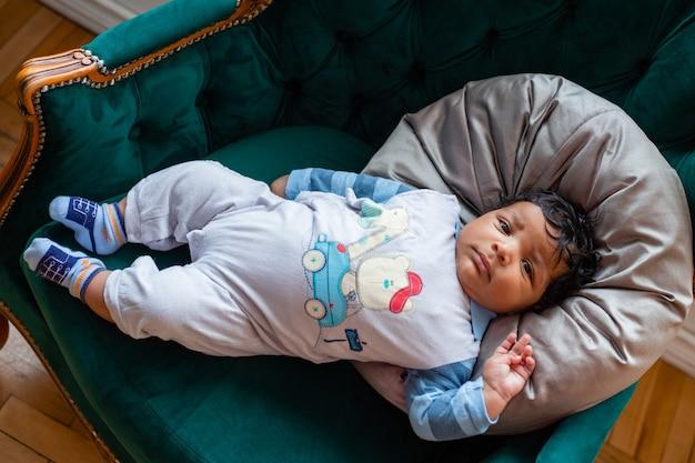 Serieuze donkere baby ligt op een kussen bovenaanzicht