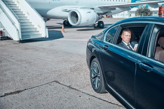Serieuze elegante man is aan het berichten op gadget terwijl hij na de landing door een chauffeur wordt vervoerd
