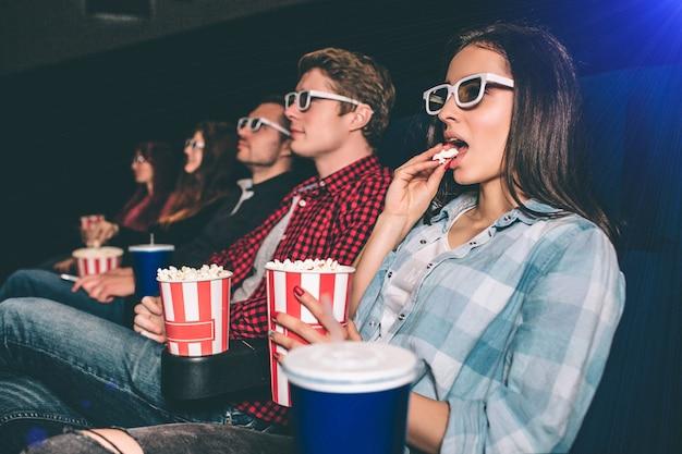 Serieuze en geconcentreerde mensen kijken naar films. ze zitten op een rij. donkerbruin meisje heeft een mand met popcron en eet het op. de andere mensen kijken gewoon een film