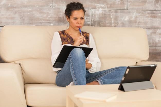 Serieuze freelancer die vanuit huis werkt tijdens een videogesprek op tabletcomputer.