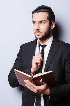 Serieuze gedachten. nadenkende jongeman in formalwear die een notitieblok vasthoudt en zijn kin aanraakt met een pen terwijl hij tegen een grijze achtergrond staat