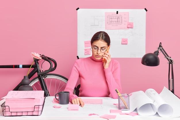 Serieuze hardwerkende vrouwelijke ontwerper praat via smartphone met collega over ideeën en communiceer creats kaart van stadslandschap poses op desktop blauwdruk in muur. werkconcept.