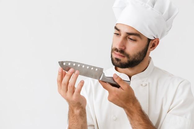 Serieuze hoofdman in kookuniform met een groot scherp metalen mes geïsoleerd over een witte muur