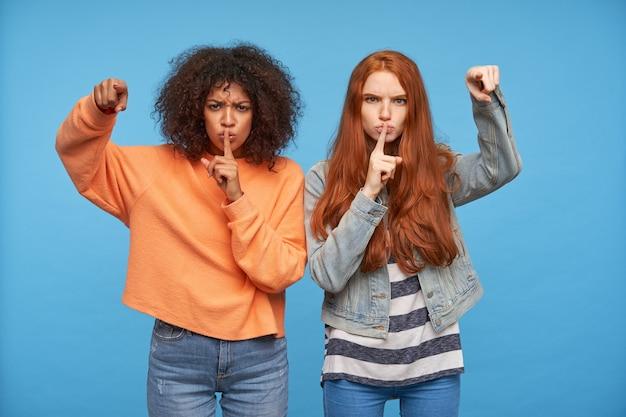 Serieuze jonge aantrekkelijke vriendinnen tonen met opgeheven wijsvingers terwijl ze streng kijken, vragen stil te zijn terwijl ze poseren voor de blauwe muur