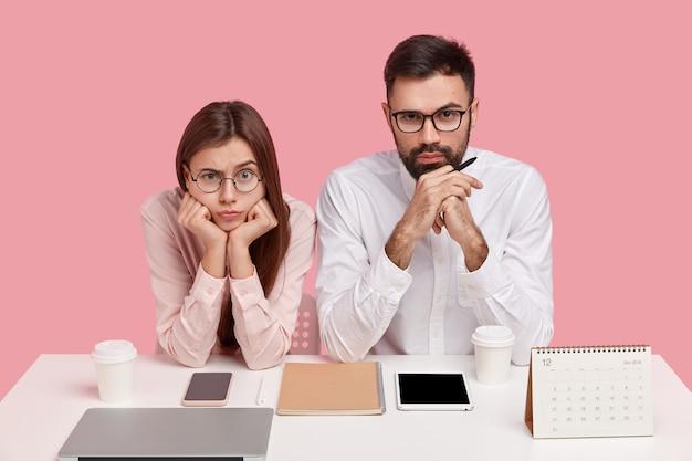 Serieuze jonge collega's denken aan een gemeenschappelijke oplossing, kijken direct, gekleed in stijlvolle kleding, houden hun kin vast