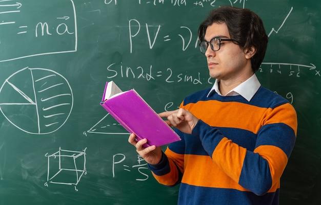 Serieuze jonge geometrieleraar met een bril die voor het bord in de klas staat en een boek leest met de vinger erop