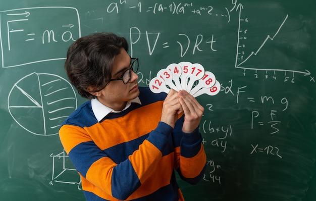 Serieuze jonge geometrieleraar met een bril die voor het bord in de klas staat en naar nummerfans kijkt