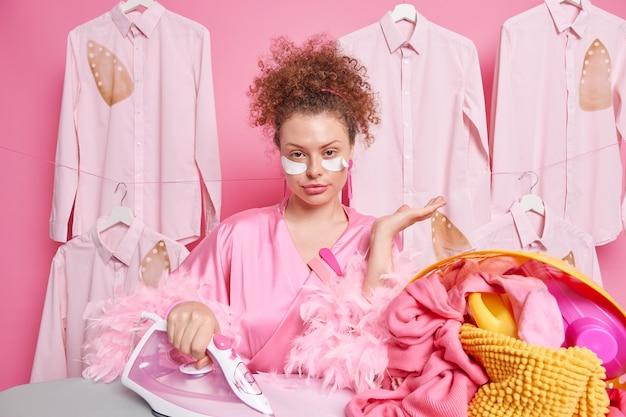 Serieuze jonge huisvrouw draagt huisjurk die bezig is met het strijken van de was ondergaat schoonheidsprocedures thuis poseert tegen gestreken overhemden op hangers die bezig zijn met huishoudelijke klusjes. huiselijk leven concept.