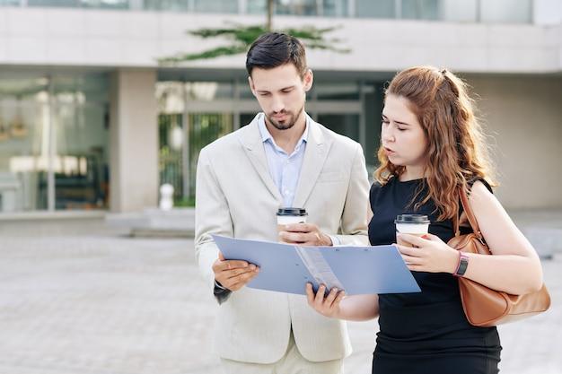 Serieuze jonge ondernemers die buiten staan met koffiekopjes en samen documenten in de map lezen
