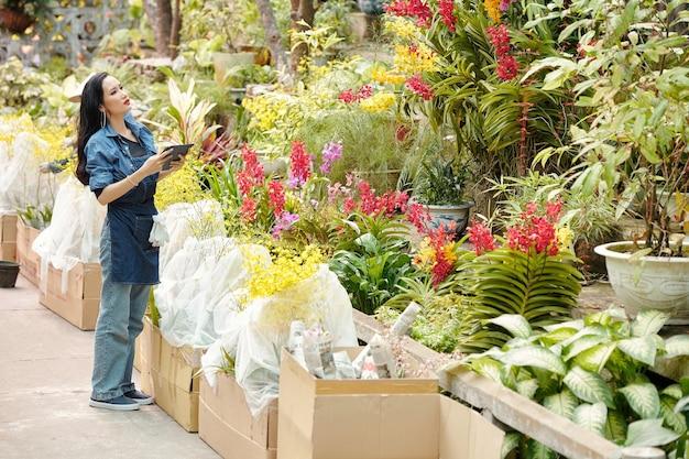 Serieuze jonge vietnamese vrouw met digitale tafel op zoek naar plant of bloem in kas om bestelling voor klant te verzenden